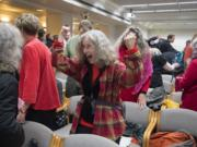 Carol Seaman of Citizens for a Clean Harbor, center, celebrates the EFSEC council ruling with fellow opponents of the Port of Vancouver oil terminal at the John A. Cherberg Building in Olympia on Tuesday afternoon, Nov. 28, 2017.