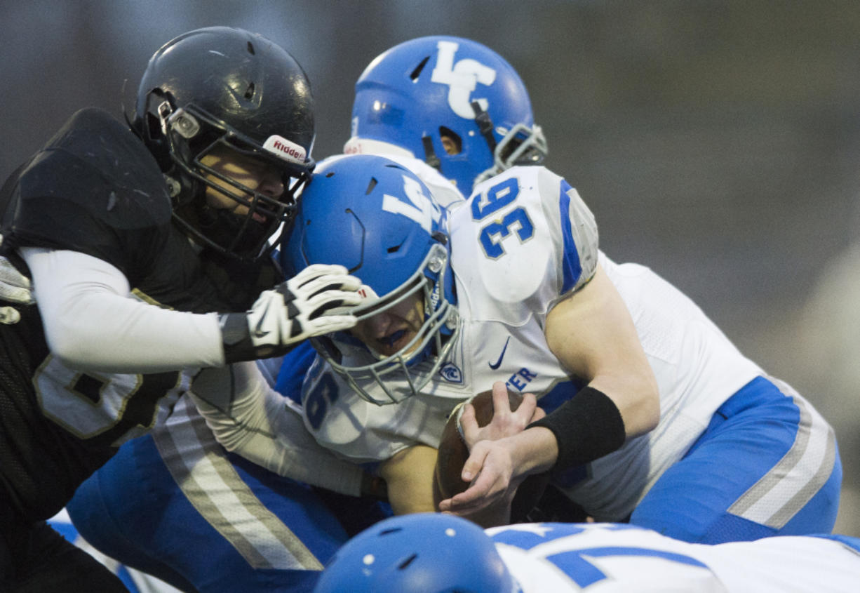 La Center's Wyatt Dodson is tackled by Meridian's Manny Sabalza on Saturday, Nov. 25, at Civic Stadium in Bellingham.
