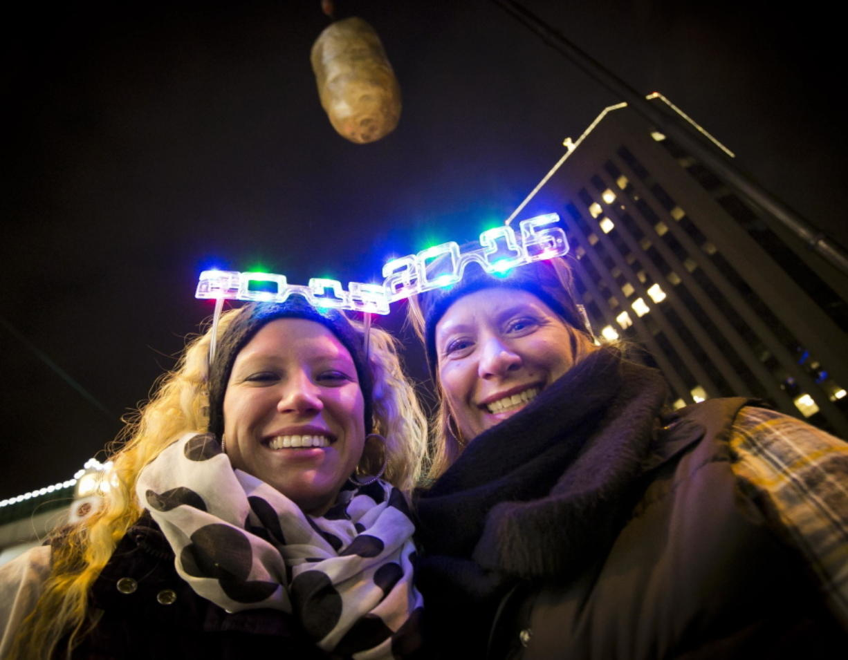 FILE--In this Dec. 31, 2014, file photo, Shelby Besler left, and her mother Tracey Besler, smile for a photograph on New Year's Eve as revelers ring in 2015 with the second annual Idaho Potato Drop in downtown Boise, Idaho. The Idaho Potato Commission has upped its sponsorship to $50,000 for the event, where a giant potato drops out of the sky as a countdown to the new year, that's now in its fifth year and keeps gaining more attention.