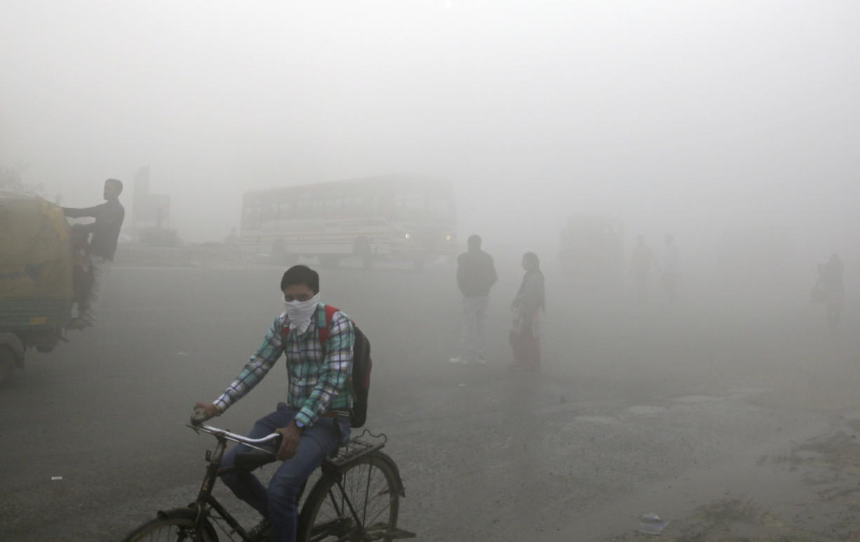 Indian commuters wait for transport amid thick blanket of smog on the outskirts of New Delhi, India, Friday. As air pollution peaked this week in Delhi, it rose to more than 30 times the World Health Organization's recommended safe level. Experts have compared it to smoking a couple of packs of cigarettes a day. A recent report by the Lancet medical journal estimated that a quarter of all premature deaths in India, some 2.5 million each year, are caused by pollution.