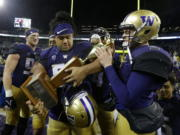 Washington quarterback Jake Browning, right, and defensive lineman Vita Vea, center, hold the Apple Cup trophy after Washington defeated Washington State 41-14 in an NCAA college football game, Saturday, Nov. 25, 2017, in Seattle. (AP Photo/Ted S.