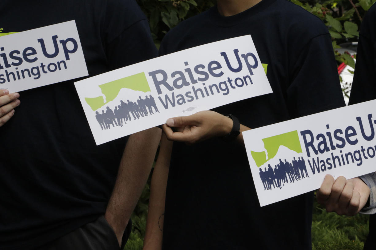 Supporters of raising the state minimum wage hold signs at a news conference, in 2016 in Olympia. Initiative 1433, approved by votes, incrementally increases the state's rate over the next four years to $13.50 an hour and to provide paid sick leave to employees who don't currently have it.