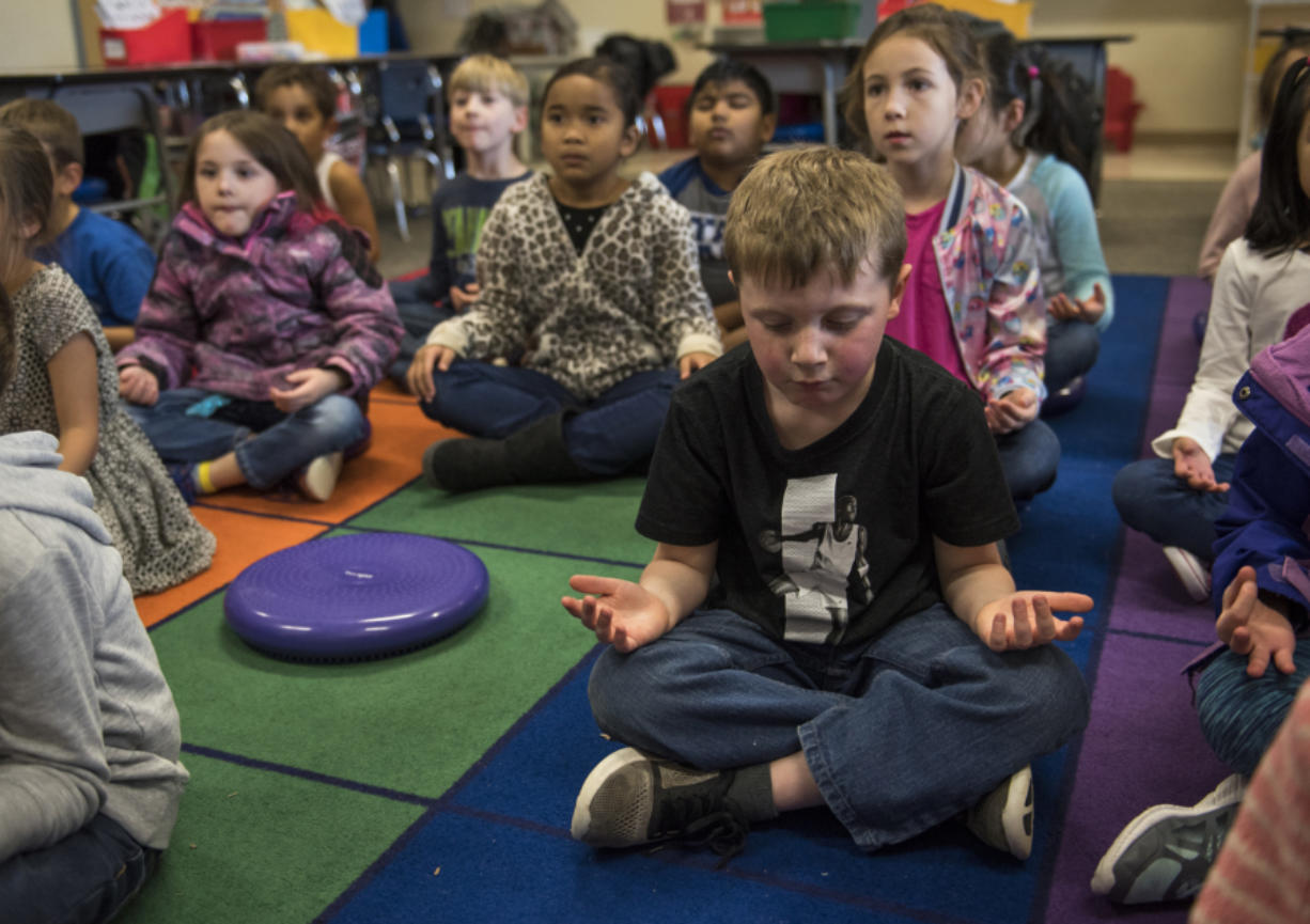 Carter Griffin closes his eyes during a mindfulness exercise after recess in Katrina Munro's first-grade classroom at Illahee Elementary School earlier this month. Evergreen Public Schools classrooms are incorporating mindful meditation into their day-to-day activities. The goal is to get students conscious of their thinking and behavior, calm and focused, and less stressed in the classroom. (Alisha Jucevic/The Columbian)
