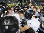 Hockinson surrounds quarterback Canon Racanelli as they celebrate their win against Tumwater after the 2A state football championship game Saturday, Dec. 2, 2017, in Tacoma, Wash.