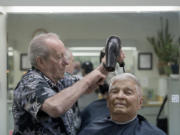 Bob Lutz, owner of Arlo's Barber Shop, keeps longtime customer Ken Powell of Vancouver looking sharp with a quick haircut on Dec. 6. Lutz has been cutting hair for nearly 60 years.