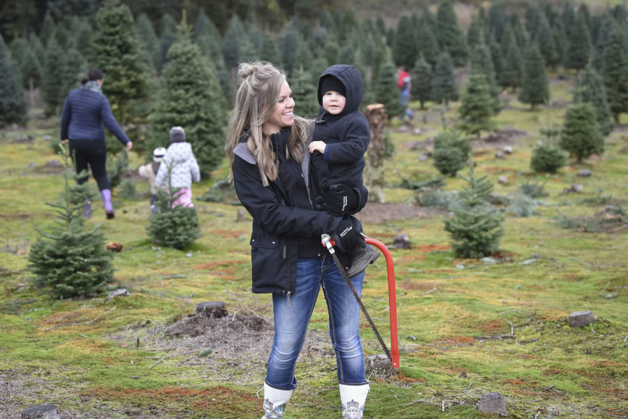 Amanda Hepner holds son Cohen Hepner after choosing a Christmas tree at  Glenwood Tree Farm. - Fewer Trees For Grinch To Steal The Columbian