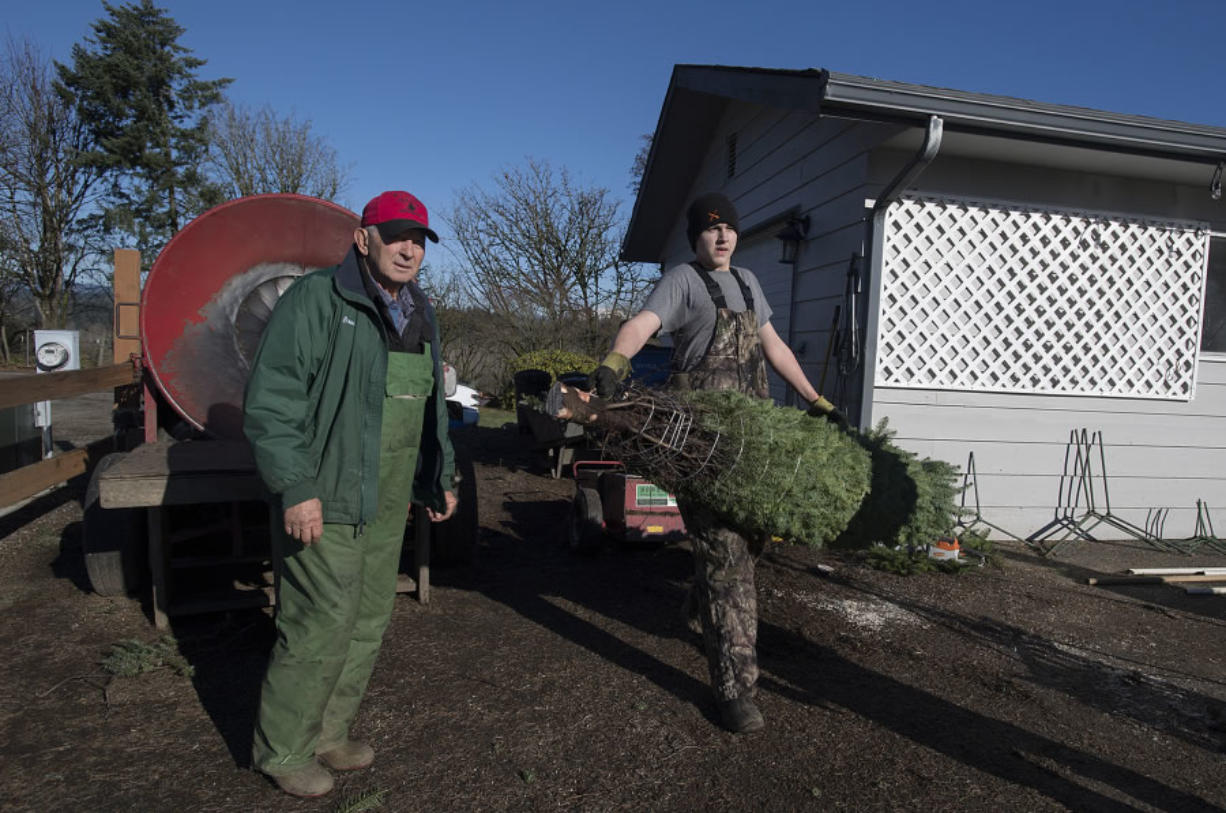 Bruce Wiseman, left, and neighbor Sean Morris help a customer with their tree at The Tree Wisemans in Ridgefield. (Amanda Cowan/The Columbian)