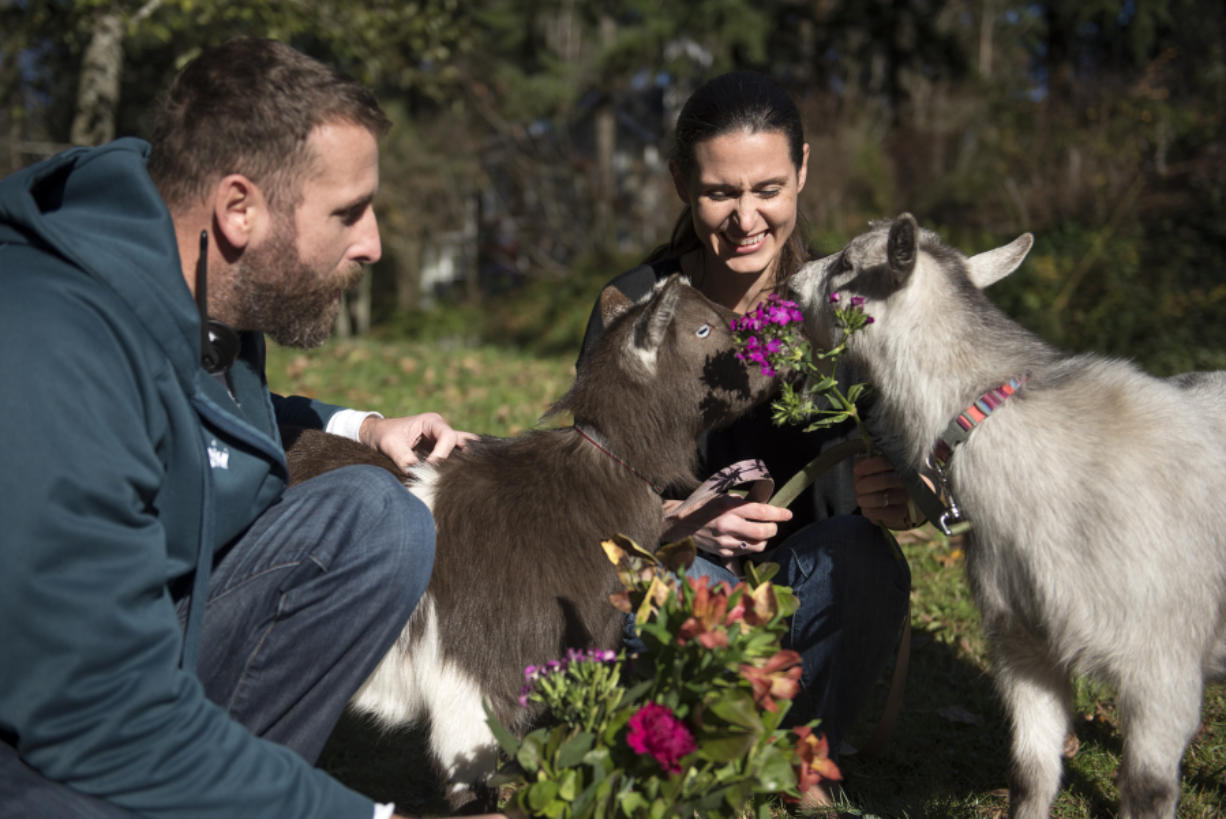 Tyler Alexander and his wife Ginny Garcia-Alexander feed flowers to Om Nom and Nibbles outside their home in Portland.