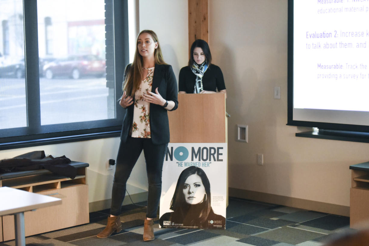 WSU Vancouver student Kelsie Reef, left, presents her team's campaign to a group of judges and WSU Vancouver students Tuesday during the Washington Says No More campaign presentations, while her teammate Melanie Shelton prepares at the lectern behind her at Pacific Continental Bank in Vancouver.