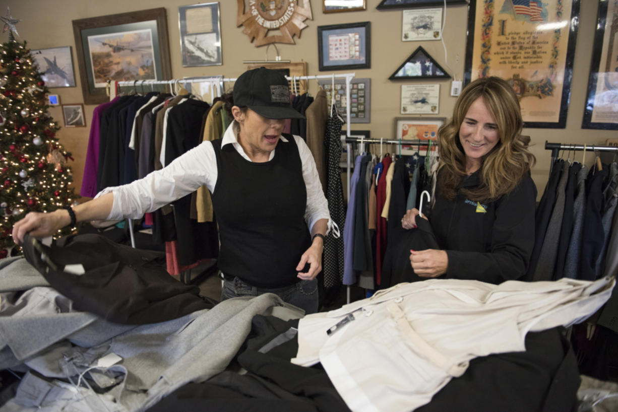 Navy veteran Jana Glover, left, of Vancouver picks out clothes Friday morning during the Suits for Soldiers event at Veterans of Foreign Wars Post 7824. She is assisted by Paula Dieringer with ServiceMaster of Portland.