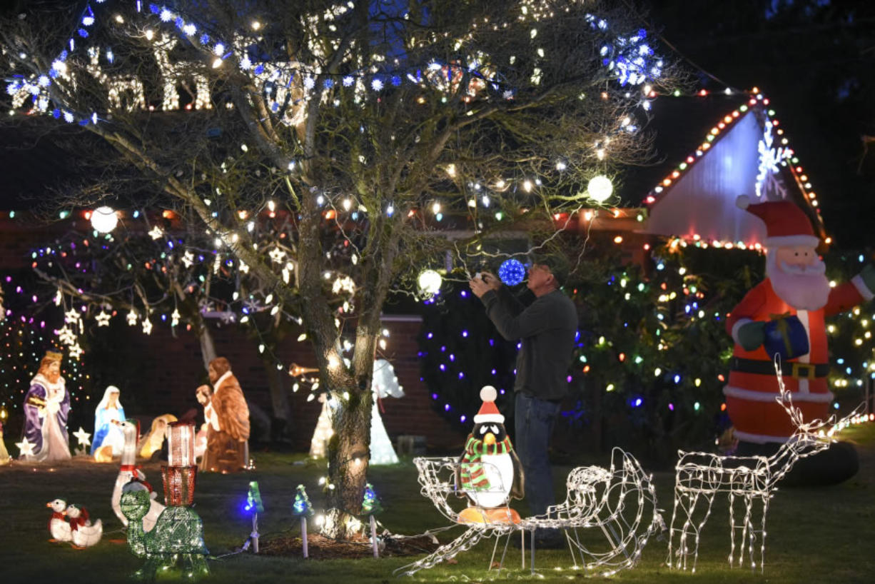 Rick Amies fixes a string of lights in the front yard of his Hazel Dell home, which is decorated with various Christmas decorations and lights, continuing a family tradition started by his parents in the Lincoln neighborhood.