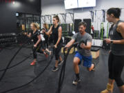 Jessica Denise, from left, Molly Maher and Jonathan Beckstead listen to directions from instructor Kathrine Kofoed at Burntown. The new high-intensity fitness studio opened in east Vancouver last month.