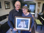 Les Burger, 77, and his wife, Julie Burger, 78, hold a portrait from their wedding in 1960 in their Vancouver home on Dec. 12. Julie, who was diagnosed with Alzheimer's disease last year, can't remember her wedding day.