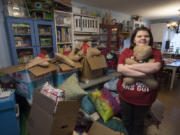 Vancouver resident Lucy Crouse, 10, is surrounded by some of the quilts and stuffed toys she made for Second Step Housing. Lucy, who has autism, has sewn 105 quilts and dozens of other gifts this year to donate to the Vancouver nonprofit.