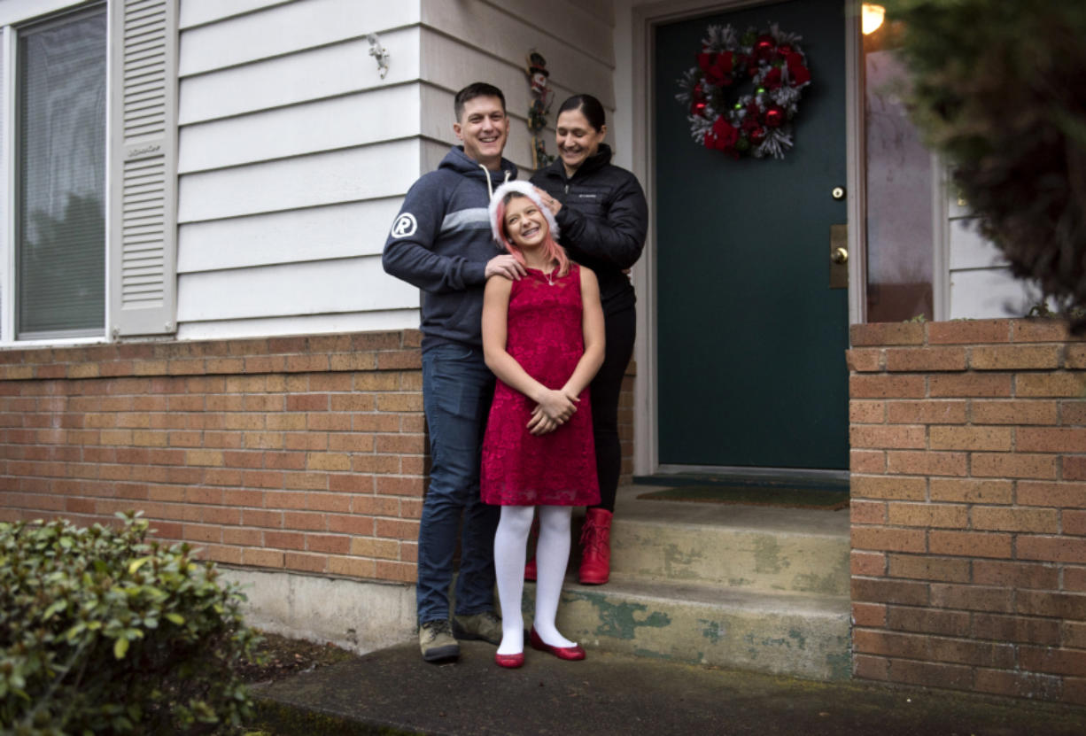 Will Mantz, left, and his wife, Jannea, right, stand outside their house with their daughter Ari. They rent their home and are hopeful the housing market will balance out soon so they can buy.