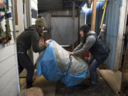 Shawn Riley, left, and Ashley LeGall move a deflated raft into the Goodwater Boat Works shop in Vancouver.