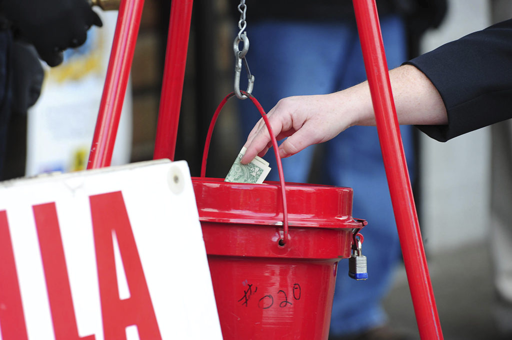 FILE - In this Nov. 22, 2017, file photo, a patron donates money in a Salvation Army red kettle in Wilkes-Barre, Pa.