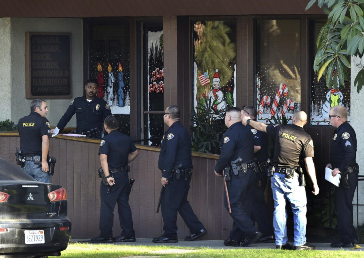 Police officers gather in front of law offices where a deadly shooting took place Friday in Long Beach, Calif.