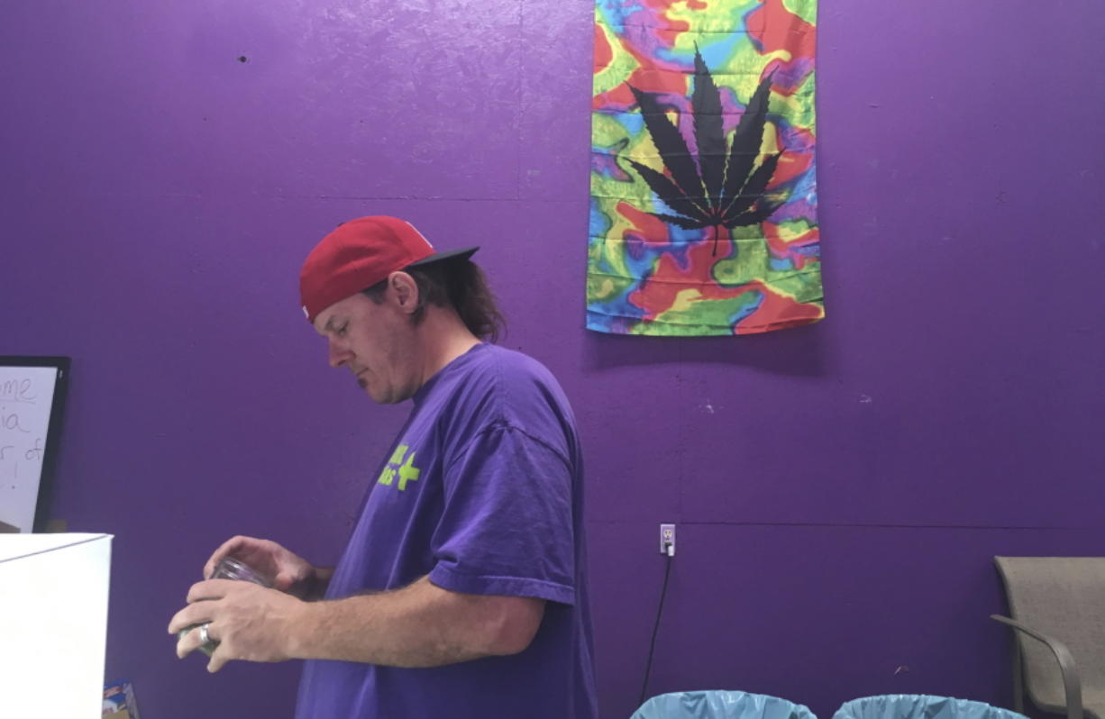 """In this Tuesday, Oct. 3, 2017, photo, Thomas Grier works as a """"bud tender"""" at Canna Can Help Inc., a medical marijuana dispensary in Goshen, Calif. Labor unions are vying to represent California cannabis workers when a new law takes effect in 2018 legalizing the sales of recreational marijuana. (AP Photo/Scott Smith)"""