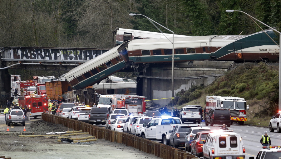 In this Dec. 18, 2017, file photo, cars from an Amtrak train lay spilled onto Interstate 5 below as some remain on the tracks above in DuPont, Wash. The train derailment which left three people dead was among the top news stories in Washington state in 2017.