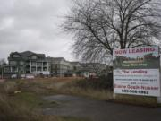 Springwood Landing, left, is seen under construction as a sign advertises space at a nearby commercial development. Springwood Landing is 80 percent pre-leased and won't open for at least four months.
