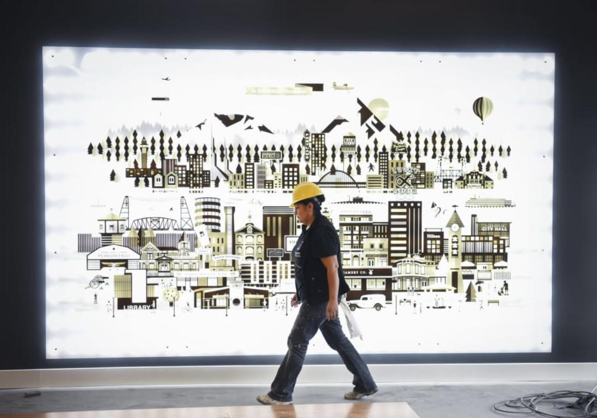 Angeles Lopez walks past artwork detailing Portland and Vancouver while preparing to paint in the lobby of The Uptown apartments on Wednesday. The complex is expected to open fully by the end of the month. (Ariane Kunze/The Columbian)