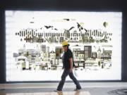 Angeles Lopez walks past artwork detailing Portland and Vancouver while preparing to paint in the lobby of The Uptown apartments on Wednesday. The complex is expected to open fully by the end of the month.