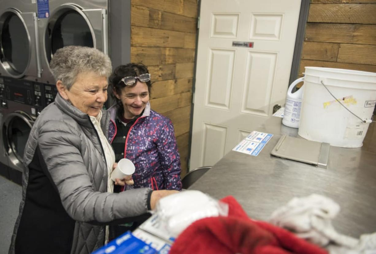 Volunteer Bert Day of Vancouver helps Deana Lentz, homeless in Vancouver, start up a loaded washer during the free laundry night at Laundry Love on Thursday evening, Jan. 4, 2018. The laundromat opened this winter after undergoing repairs from an accident in May.