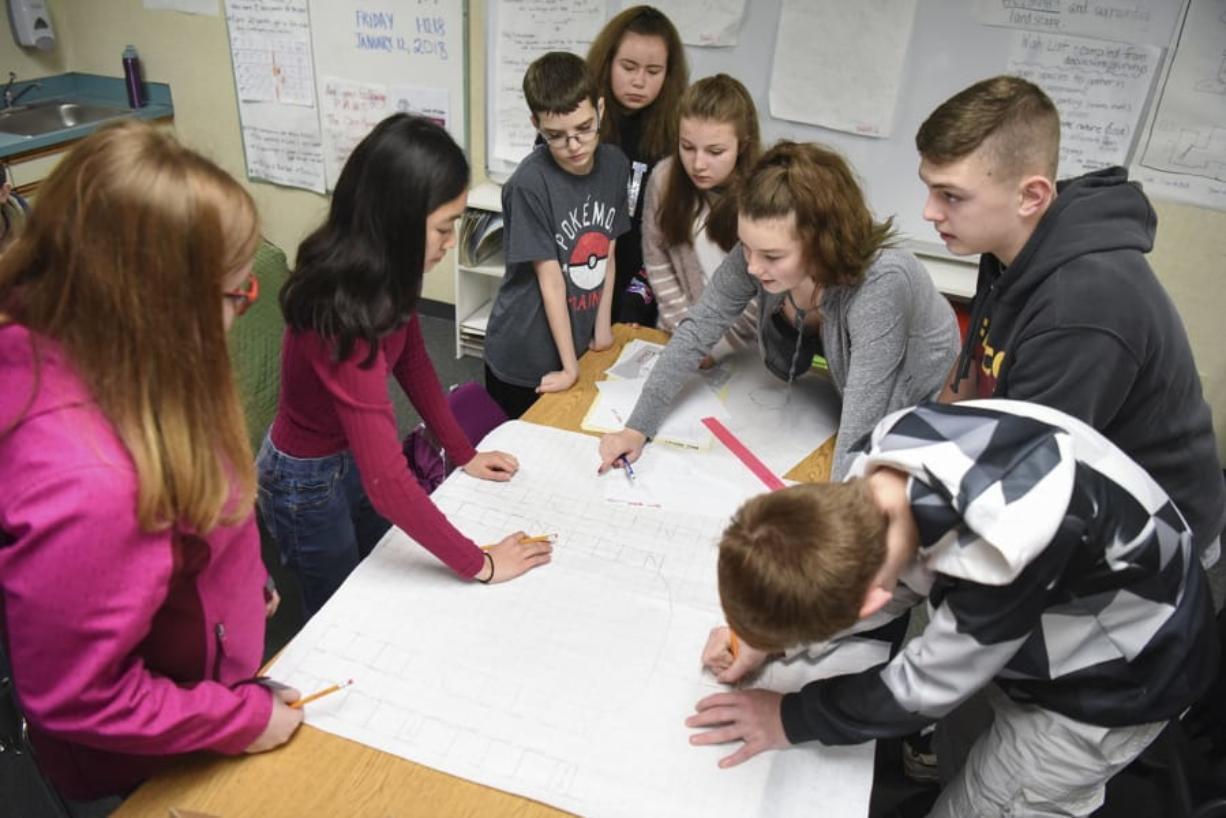 Eighth-graders at Laurin Middle School work together on design plans for their new middle school Friday during their hands-on science elective class led by Joan Smith. Students are split into different teams to design an imagined version of the Brush Prairie school.