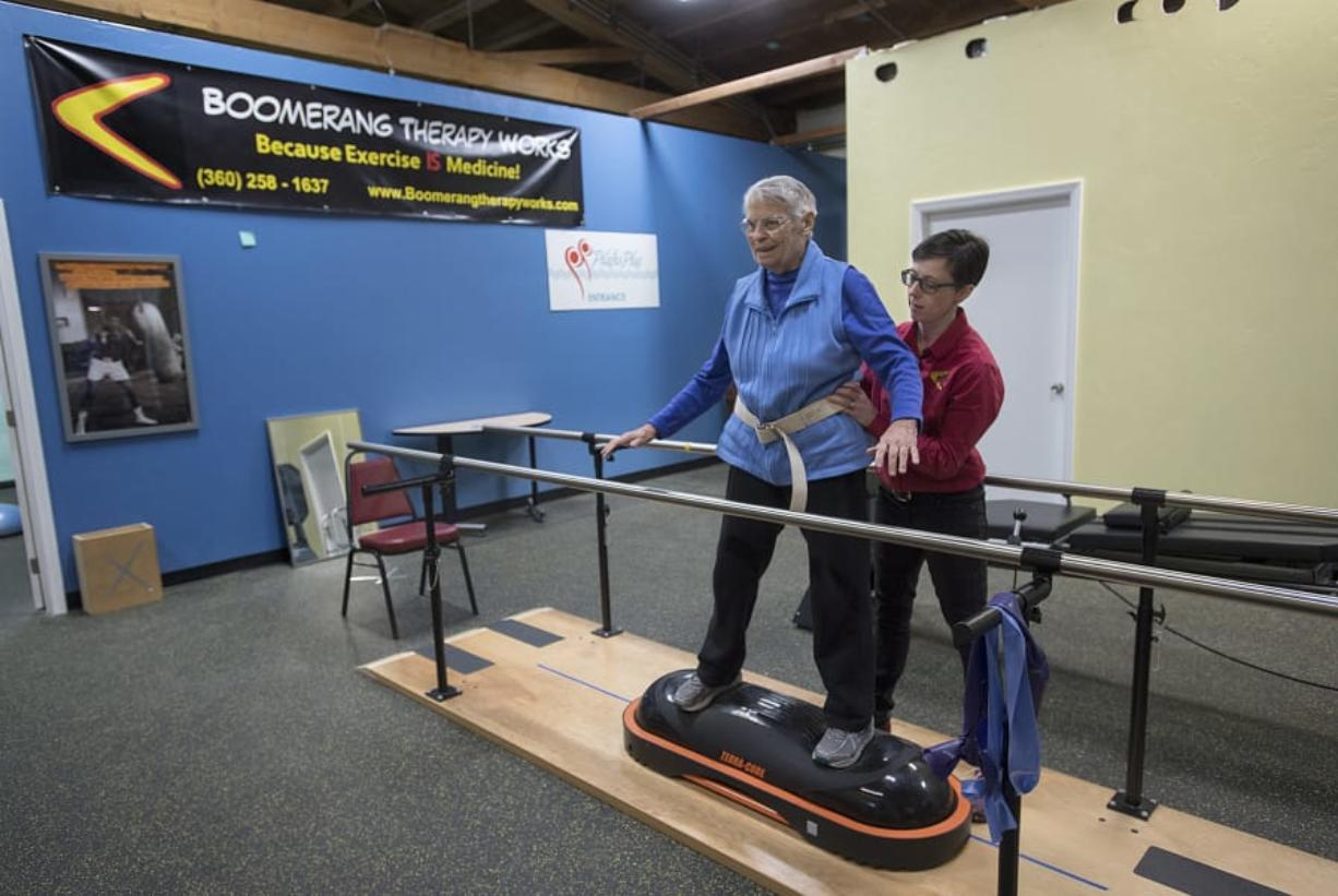 Physical therapist JJ Flentke helps patient Cathy Monbrod of Vancouver to balance during an exercise Tuesday morning at Boomerang Therapy Works in Vancouver. Flentke opened the gym, which focuses on keeping seniors active, in June.