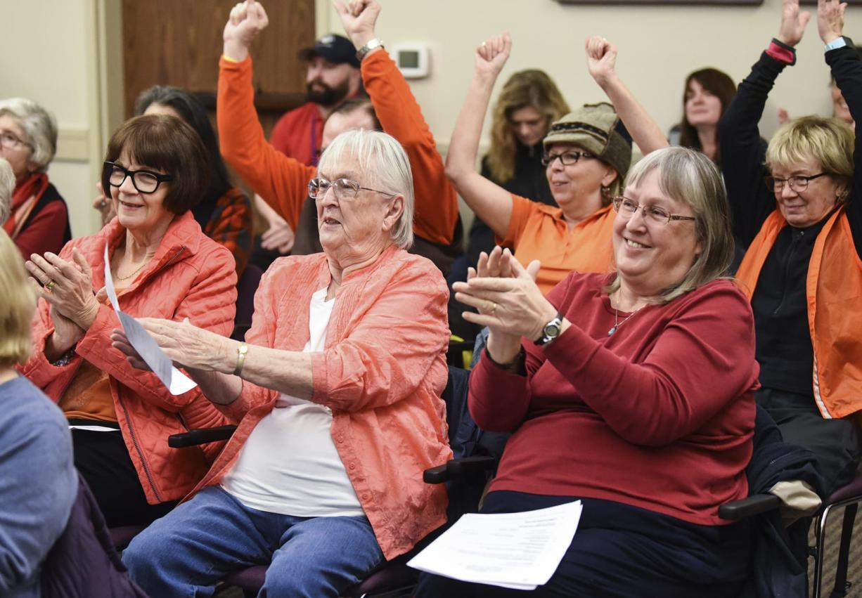 Lethene Parks, center, and Carrie Parks, right, applaud and cheer following the Port of Vancouver's board of commissioners' unanimous decision to put an end date on Vancouver Energy's rolling lease for a proposed oil terminal, Tuesday January 9, 2018, at the Port of Vancouver. (Ariane Kunze/The Columbian)