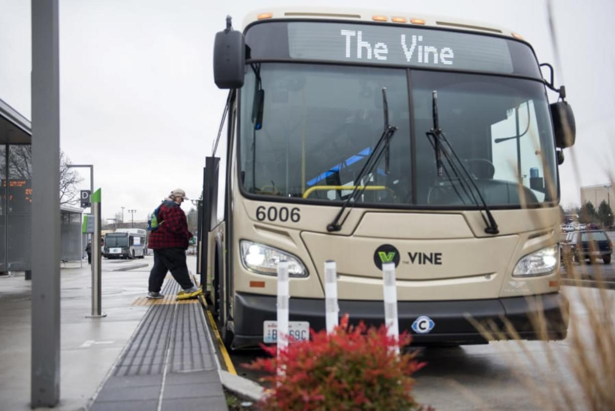 Vancouver resident and regular C-Tran rider Cathy Chidester of Vancouver boards a Vine bus at the Vancouver Mall Transit Center on Tuesday afternoon. Tuesday marked the first anniversary of The Vine, C-Tran's bus rapid transit system. Agency officials say The Vine is faster, more efficient and serves more people than the traditional bus route it replaced. (Alisha Jucevic/The Columbian)