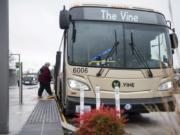 Vancouver resident and regular C-Tran rider Cathy Chidester of Vancouver boards a Vine bus at the Vancouver Mall Transit Center on Tuesday afternoon. Tuesday marked the first anniversary of The Vine, C-Tran's bus rapid transit system. Agency officials say The Vine is faster, more efficient and serves more people than the traditional bus route it replaced.