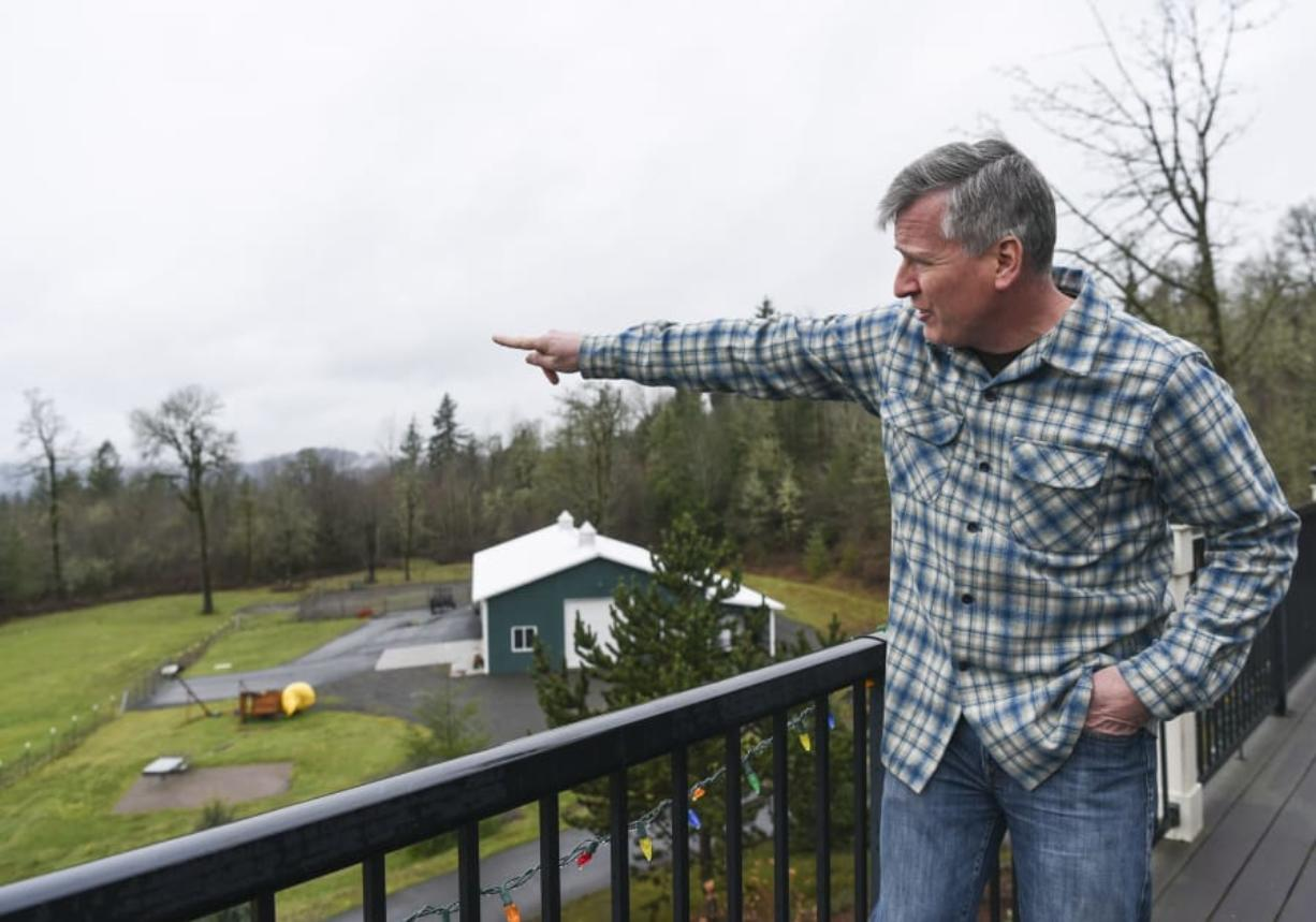 Sean Streeter points toward a gravel pit across Gibbons Creek that he says has disturbed the peace and quiet his family has enjoyed living outside of Washougal. (Ariane Kunze/The Columbian)
