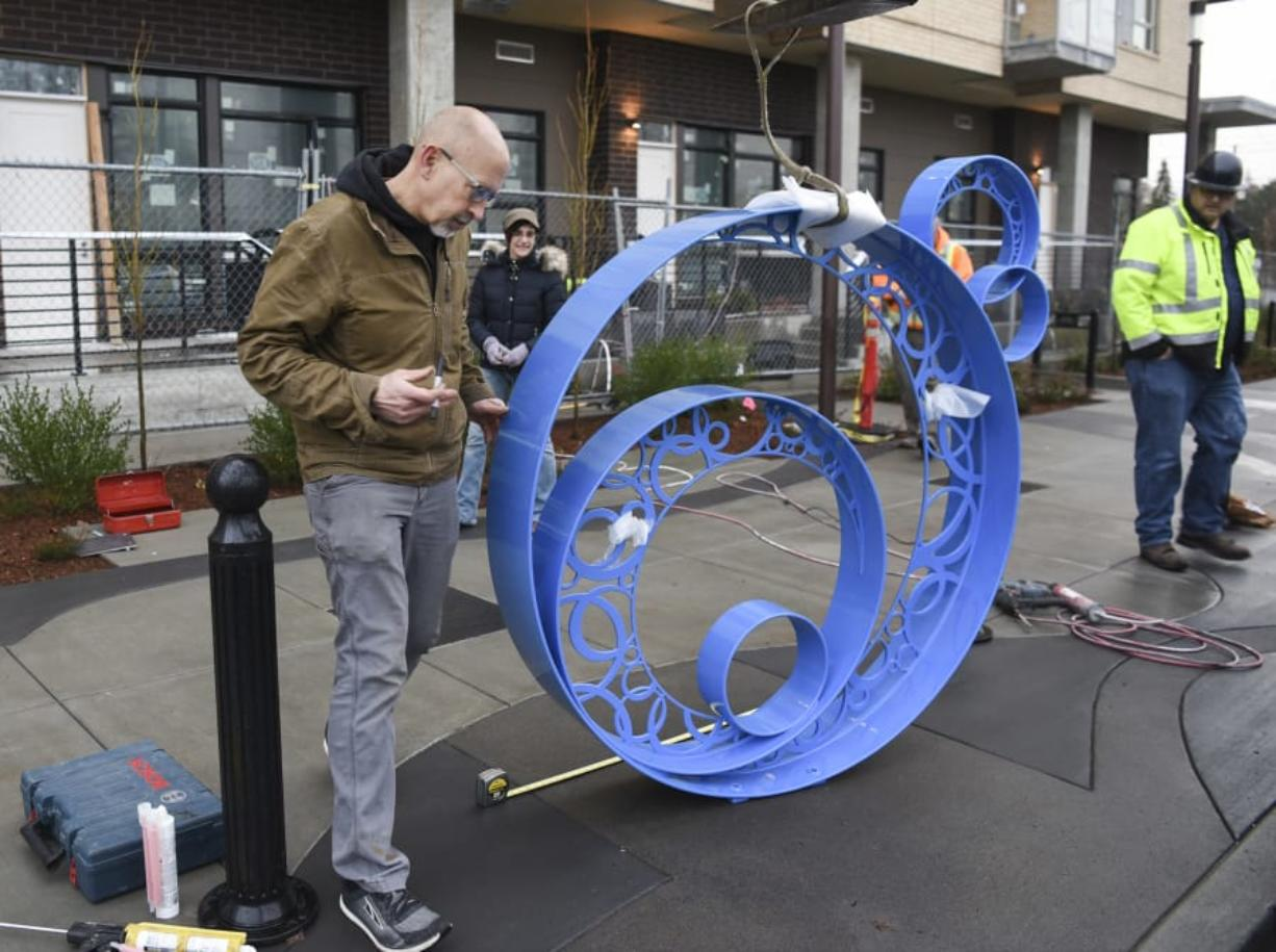 "Builder Dave Frei, left, and designer Jennifer Corio, the husband-and-wife team known as Colbalt Designworks, consider the placement of their metal sculpture ""Bubbles"" on the Washington Street sidewalk outside The Uptown Apartments, which is shortly to open to tenants.  (Ariane Kunze/ The Columbian)"