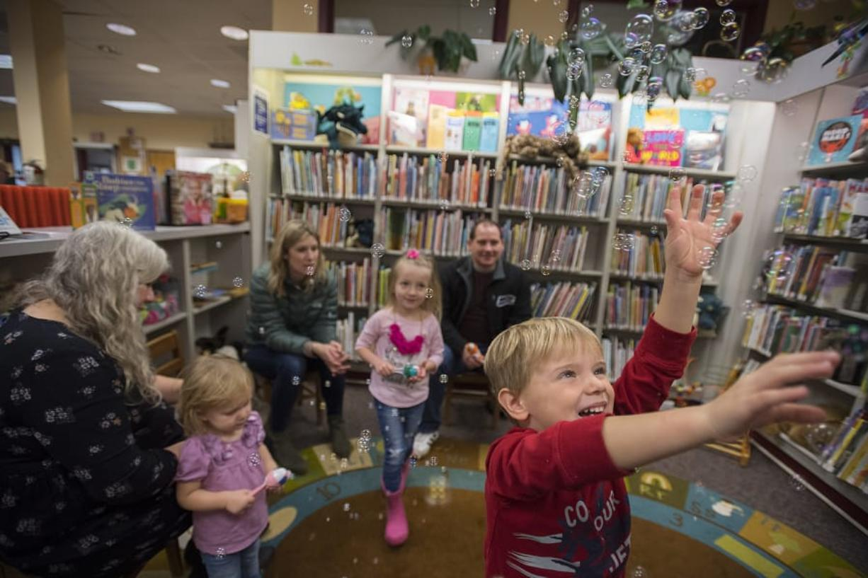 James Tobin, 4, of Ridgefield, in red, joins other participants in children's story time as they enjoy playing with bubbles at Ridgefield Community Library.