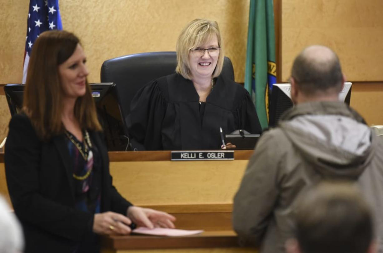 Defense attorney Lisa Toth, left, listens as Judge Kelli E. Osler, center, chats with a Mental Health Court participant Wednesday during a compliance review in Clark County District Court. (Ariane Kunze/The Columbian)