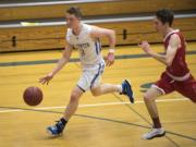 La Center's Saige Keep (3) dribbles down court followed by Columbia-White Salmon's William Gross (14) during Tuesday night's game at La Center High School on Jan. 30, 2018. La Center defeated Columbia-White Salmon 88-78.