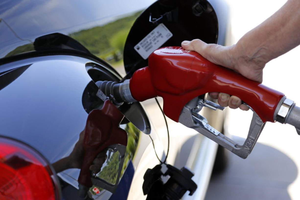 FILE - In this Thursday, July 16, 2015, file photo, a customer re-fuels her car in Robinson Township, Pa. New government data shows gas mileage for 2016 model year light-duty vehicles sold in the United States made smaller than expected gains in fuel economy over the last year, though new cars are generally sipping less gas and spewing less plant-warming carbon emissions than their predecessors. The Environmental Protection Agency released its latest annual CO2 fuel economy trends Thursday, showing 2016 vehicle fuel economy was 24.7 mpg, higher than model year 2015 by only one-tenth of a gallon. (AP Photo/Gene J. Puskar, File)