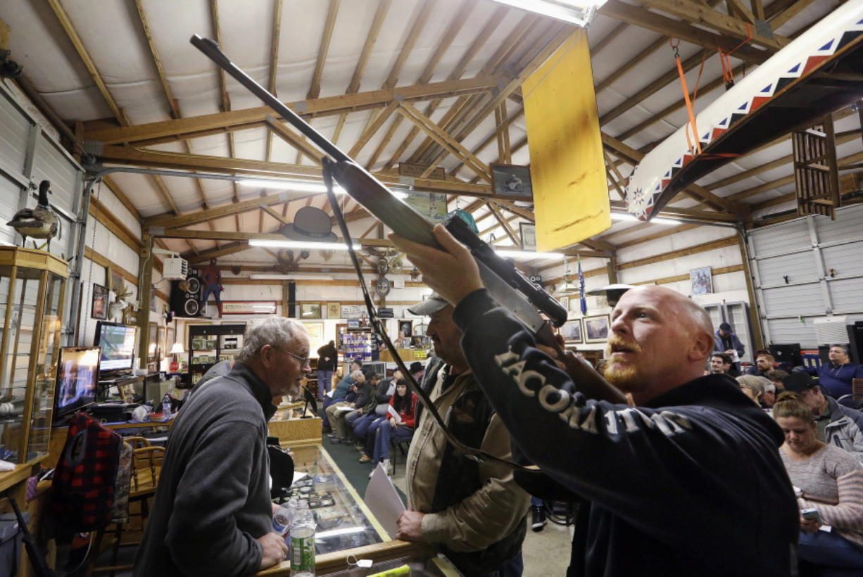 Customer Andy Muscato looks over a rifle on Oct. 20, 2017, before an auction at Johnny's Auction House, where the company handles gun sales for several police departments and the Lewis County Sheriff's Office, in Rochester, Wash.