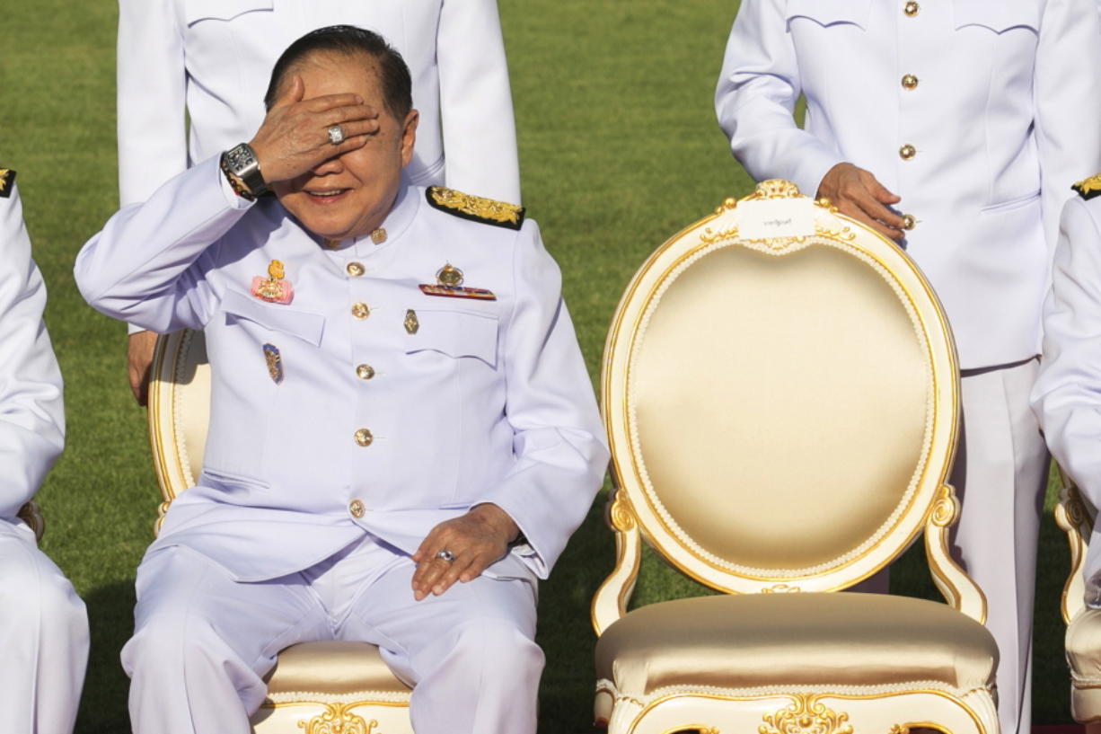 Deputy Prime Minister Prawit Wongsuwan raises his hand to shade the sun wearing a luxury watch and diamond ring Dec. 4 at Government House. Prawit has so far been spotted wearing a total of 25 opulent timepieces, none of which appears on his last declaration of assets.