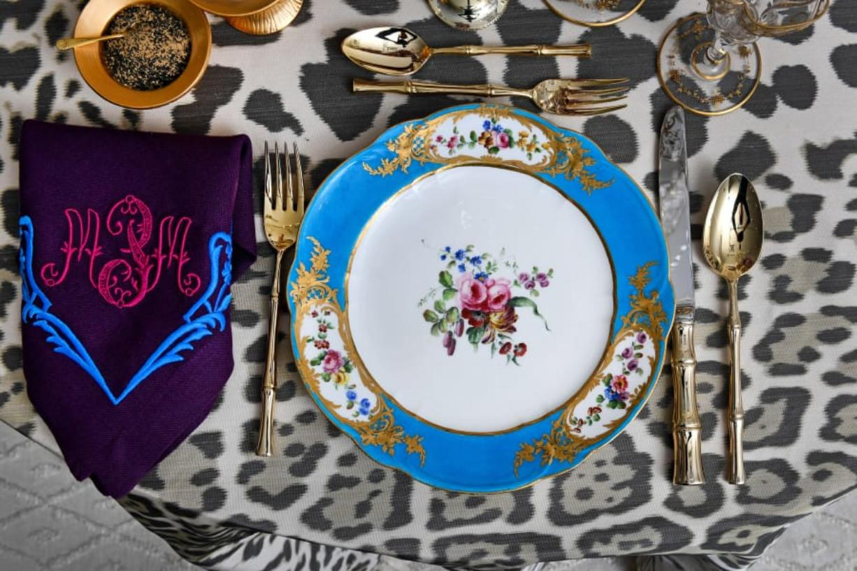 The table setting by Alex Papachristidis features Marjorie Merriweather Post's French Sevres 1768 porcelain along with a custom tablecloth and monogrammed napkins that tie into the blues, purples and pinks of the plates. The centerpiece is a handcrafted porcelain flower arrangement by Vladimir Kanevsky. The gold salt and pepper cellars are a modern design by Christopher Spitzmiller. The bamboo-handled flatware belongs to Papachristidis.