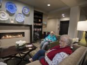 """Florence Böelow, right, and Joyce Carr relax by the fire with friends at The Lofts at Glenwood Place. Böelow, 87, recently moved from an apartment in Portland to the independent living center to be closer to her children. """"I needed some companionship,"""" she added."""
