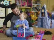 Justin Hayden listens as his daughter, Gwenyth, 5, talks about her dolls while playing together on a recent Wednesday. Gwenyth was diagnosed with acute lymphoblastic leukemia in January 2017.