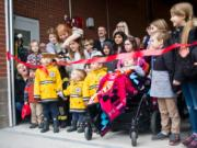 Vancouver Mayor Anne McEnerny-Ogle gets some help cutting the ribbon for Vancouver Fire Department's Fire Station 2 on Saturday. Many attended the event, including young families and children who hoped to become firefighters.