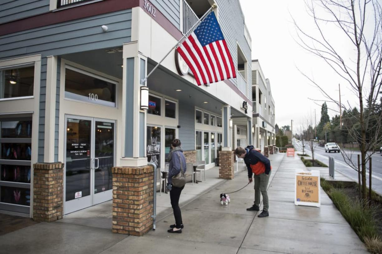 Gabby White, left, and Justin Lee, right, both of Vancouver, walk their new cocker spaniel puppy, Ripley, along the sidewalk next to Felida Village, which opened in 2015. The mixed-use development has retail space, apartments and a vacation rental. Developer Ron Edwards is now one of the people bringing a similar project to Ridgefield.