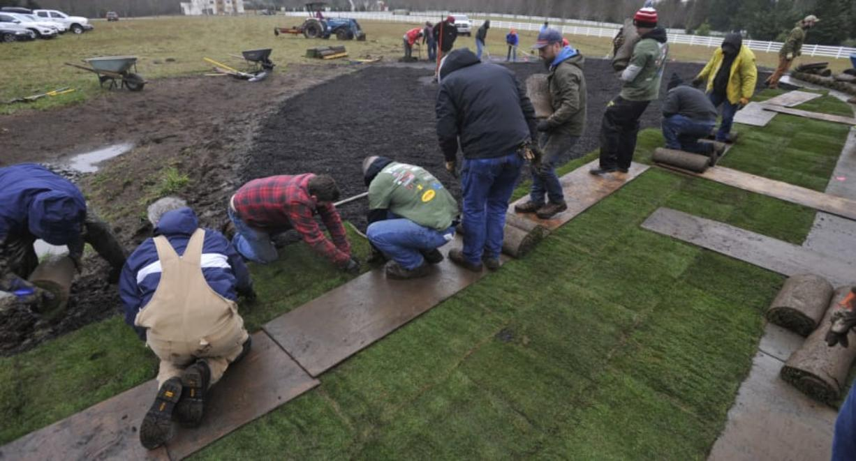 About 100 volunteers spent a soggy Saturday morning laying sod for Army Spc. Alex Hussey, who will receive the keys to a specially adapted custom home in Washougal in a few months. The home is being built and donated by the nonprofit Homes For Our Troops.