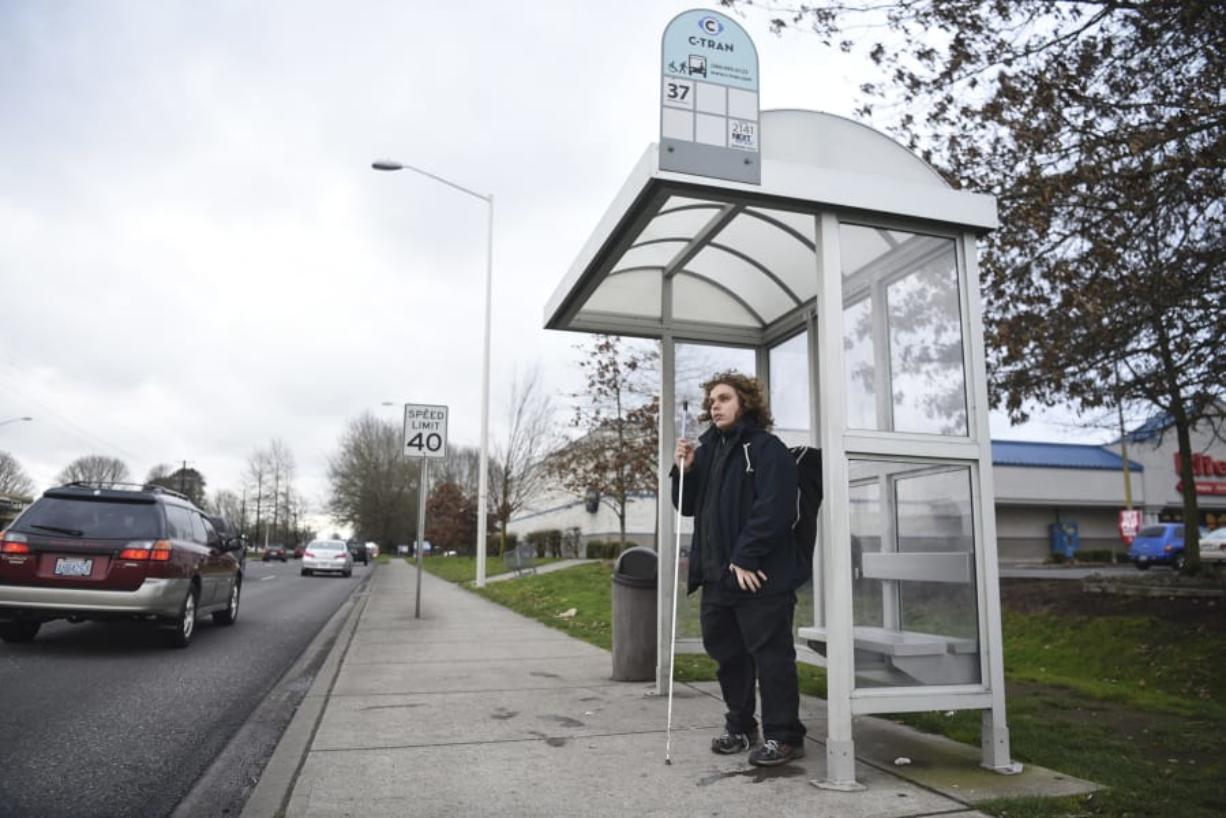 Nathaniel Baker, 19, of Vancouver, waits for the bus Friday on Mill Plain Boulevard near the intersection of Southeast 136th Avenue. C-Tran is working to develop a Mill Plain Boulevard Bus Rapid Transit corridor.