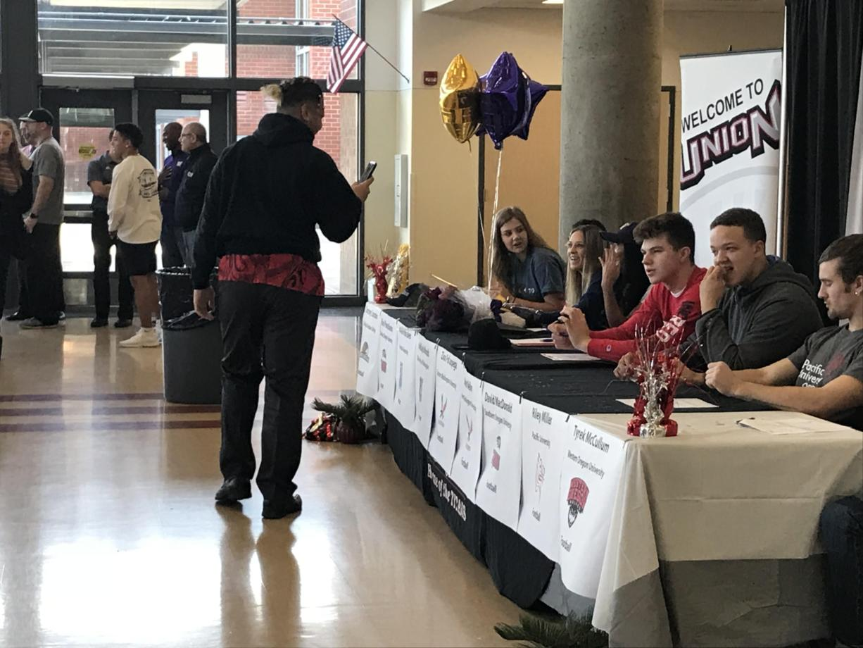 Union senior Zion Fa'aopega (left) captures the Signing Day festivities on his smartphone before the high school's ceremony began Wednesday morning. Fa'aopega and Aiden Nellor signed to play football at Eastern Washington, two of the Titans' five college-bound football players.