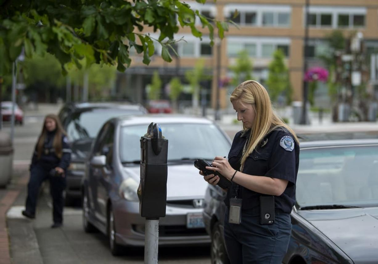 Parking enforcement officer Holly Naramore issues a ticket for an expired meter in downtown Vancouver in 2017. The city is now talking about increasing parking rates and developing demand-based fees.
